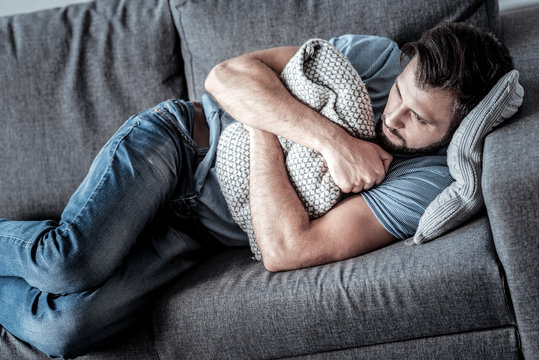 Absolute solitude. Top view of a depressed unhappy sad man lying on the sofa and hugging a cushion while feeling lonely