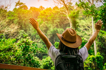 Happy woman tourist with hat and backpack standing and raise her hands up in tropical forest. Young traveler enjoy beautiful scenery.