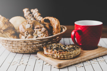 healthy eating and traditional bakery concept; fresh bread on the kitchen table with beverage at morning