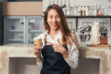 Close up of a young Asian female barista hold a cup of coffee serving to her customer with smile surrounded with bar counter background. Young female barista and her small shop. Food and drink concept