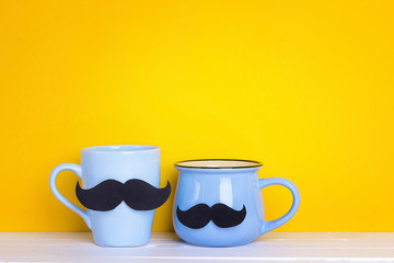 Two blue mug with a mustache on yellow background. Copy space.