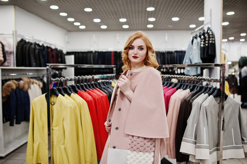 Elegance blonde girl in coat at the store of fur coats and leather jackets.