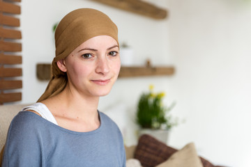 Portrait of young positive adult female cancer patient sitting in living room, smiling and looking at the camera.