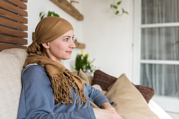 Portrait of young positive adult female cancer patient sitting in living room, smiling and watching tv.