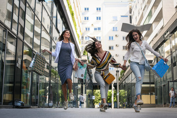 Three woman walking happy and satisfied city street after shopping.