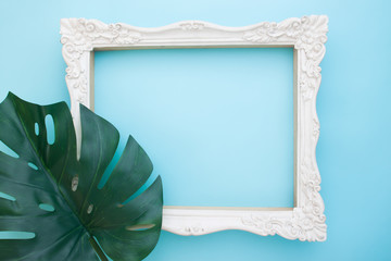 Vintage white picture flame and monstera leaf on blue color background