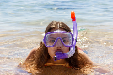 Beach vacation fun woman wearing a mask tube for swimming in ocean water. Close-up portrait of a girl in her travel holidays