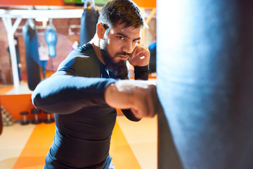 Waist up portrait of fierce Middle-Eastern fighter hitting punching bag at boxing practice in martial arts club, copy space