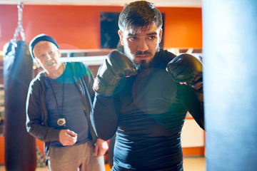 Waist up portrait of bearded Middle-Eastern fighter hitting punching bag at boxing practice in martial arts club with senior coach in background