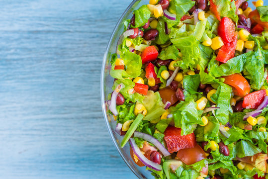 Traditional vegetarian American Southwest Salad on a glass bowl and rustic background - copy space for a recipe