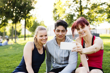 Group of young runners with a smartphone in a park.