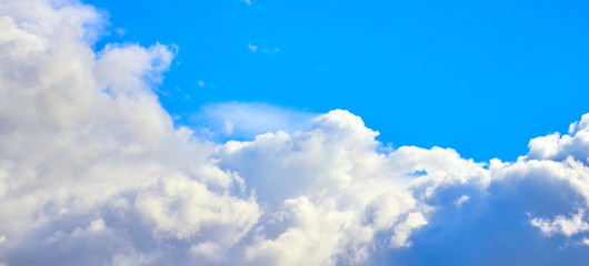white clouds of different shapes against the blue sky.