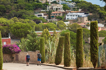 Trip to Tossa de Mar in Sapin. Two People walking with backpacks. Adventure travel.