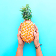 Woman's hands holding pineapple on blue color background, Summer holiday concept