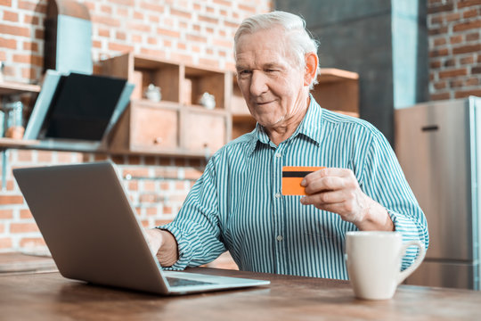 Joyful senior man using a credit card