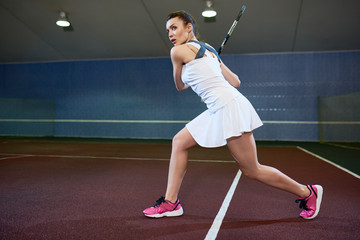 Full length portrait of determined young woman playing tennis in indoor court,  hitting ball with racket, copy space