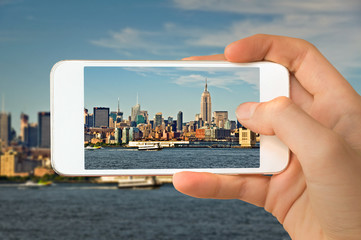 Closeup of a hand with smartphone taking a picture of  Manhattan skyline, New York USA