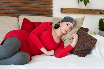 Young adult female cancer patient relaxing on a couch. Tired, exhausted, depressed cancer patient.