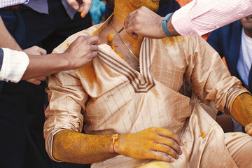 Groomsmen paint fiance with turmeric paste while he sits on the floor