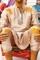 Indian groom sits on the floor lying his hands over knees covered with turmeric paste
