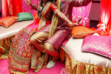 Happy Indian bride and groom raise their hands up while sitting on the golden couch