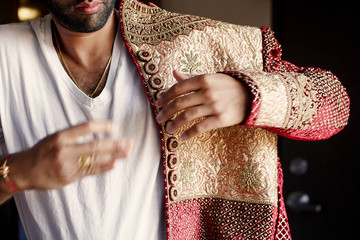 Handsome Indian groom puts on red sherwani with golden design