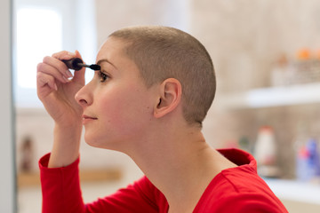 Young adult female cancer patient with gorgeous new short hair, looking in the mirror, smiling, applying mascara.