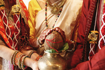 Festive dressed parents and beautiful Indian bride hold traditional coconut