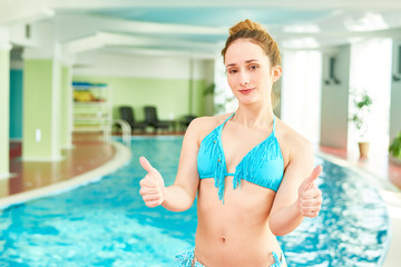 Waist up portrait of beautiful young woman in swimming pool smiling, looking at camera and showing thumb up, copy space