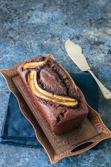 Rich chocolate banana date bread on a vintage tray on a blue stone background. Copy space.