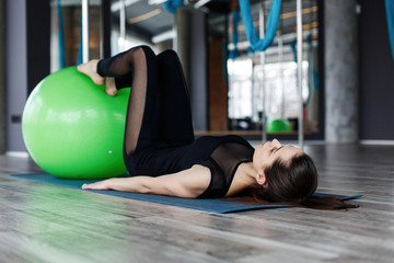 Pretty young woman flexing abdominal muscels on the green ball in gym