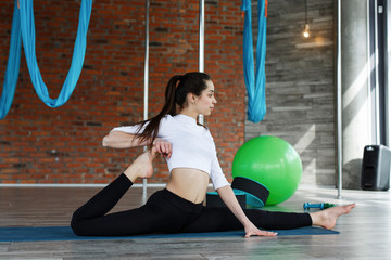Brunette girl in black and white sport clothes does yoga and stretching in the gym
