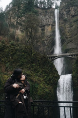 Hugging Asian couple stands before a beautiful waterfall in the mountains
