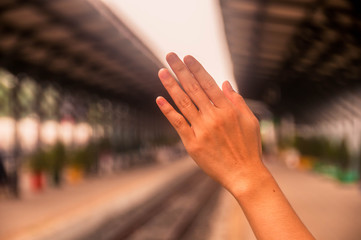 hand of human showing with old straight railway back ground at station.