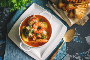 Photo Stands Ready meals French fish soup Bouillabaisse with seafood, salmon fillet, shrimp, rich flavor, delicious dinner in a white beautiful plate.