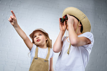 children in safari costumes and hats pointing and looking in binoculars