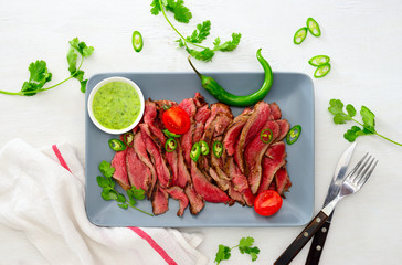 Grilled and sliced rare beef skirt steak served with green chimichurri sauce