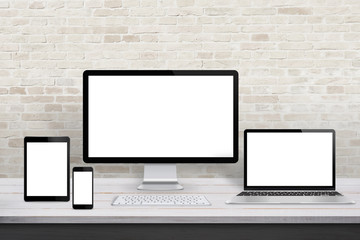 Wall Mural - Multiple display devices for responsive web desing promotion. Modern office desk with brick wall in background.