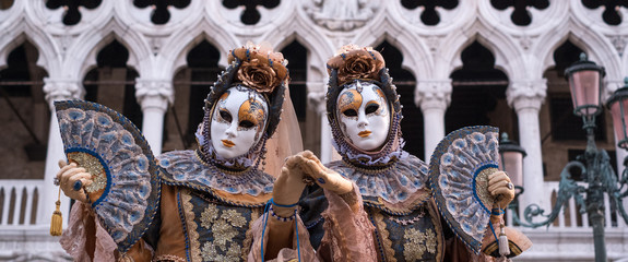 Two women in traditional costume and painted masks, with decorated fans, standing in front ofthe Doges Palace during the Venice Carnival (Carnivale di Venezia)