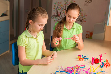 Cute little girls creating toys with chenille sticks