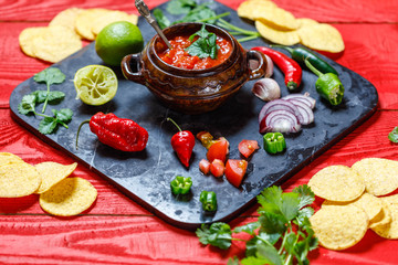 Homemade salsa with ingredients on black stone desk on red rustic background, tomato, pepper, onion, chili, habanero, coriander leaf. Mexican food concept, top view, overhead