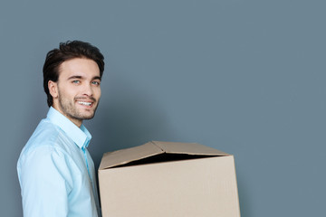 For things. Cheerful happy nice man smiling and holding the box while looking inside it
