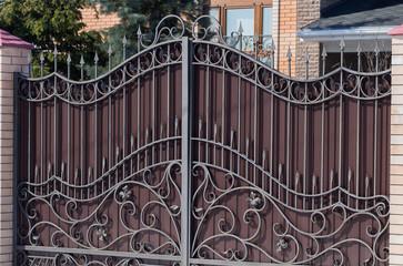 Stylish brown iron gate with a pattern and brick columns