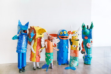 People in handmade colorful monsters costumes standing together in studio.