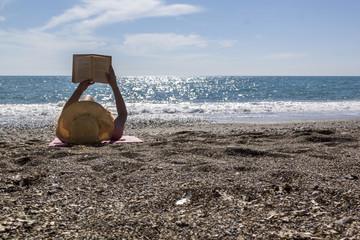 Beautiful woman reading a book on beach Antalya