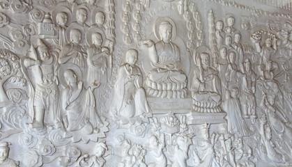 An image of a buddha and monks in a stone on a white wall, in th