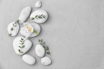 Spa stones and beautiful flower on light background