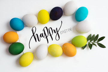 "Easter festive colorful eggs on a white background with a greeting card calligraphy ""happy easter"". eggs yellow, blue, green and blue, orange and purple"