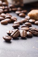 Black fried coffee beans on dark textured background