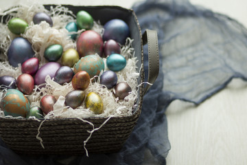 a gray basket with straw and Easter eggs